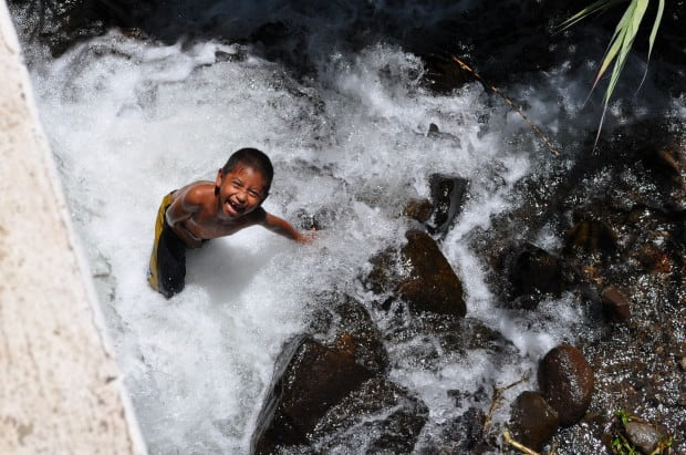 A young boy swims and plays in a waterfall in Tzununa.